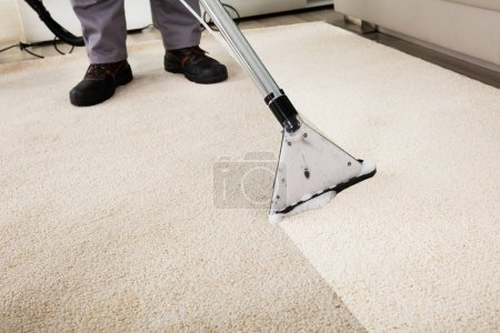 Photo for Closeup Of Person Cleaning Carpet With Vacuum Cleaner - Royalty Free Image