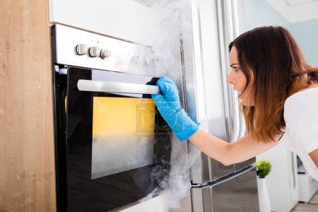 Woman Looking At Smoke Oven