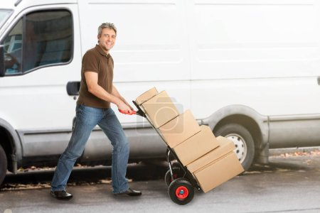 Photo for Smiling Delivery Man Pushing Parcels On HandtruckIn Front Of The Van - Royalty Free Image