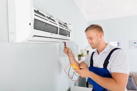 Photo pour Électricien mâle vérification climatiseur avec multimètre numérique - image libre de droit