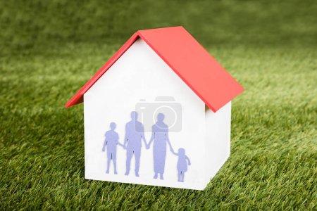 Photo pour Gros plan du modèle de maison avec la famille à ce sujet sur terrain gazonné - image libre de droit
