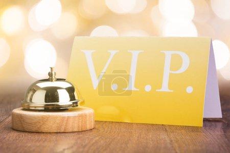 Foto de Closeup de Bell de servicio con tarjeta Vip en el mostrador de madera - Imagen libre de derechos