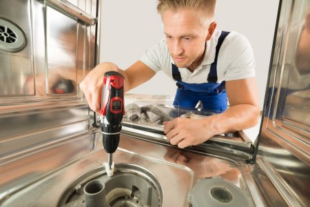Photo for Young Man In Overall Repairing Dishwasher With Electric Drill - Royalty Free Image