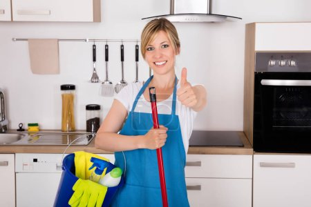 Photo for Cleaning Service Professional Housemaid Holding Gloves And Equipment In Kitchen At Home Showing Thumbs Up - Royalty Free Image