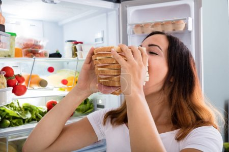 Photo for Young Woman Eating Meat Sandwich In Front Of Open Fridge - Royalty Free Image