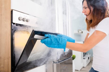 Woman Opening Door Of Oven