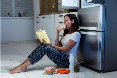 """Photo pour Livre de lecture jeune femme tout en mangeant """"sandwich"""" en cuisine - image libre de droit"""