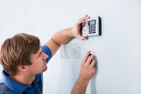 Repairman Fixing Security System
