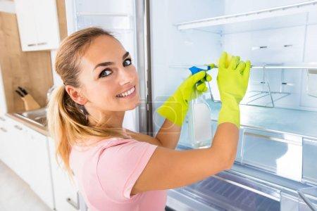 Photo pour Happy Cleaning Service Professional Femme Nettoyage vide réfrigérateur porte avec bouteille de pulvérisation et éponge - image libre de droit