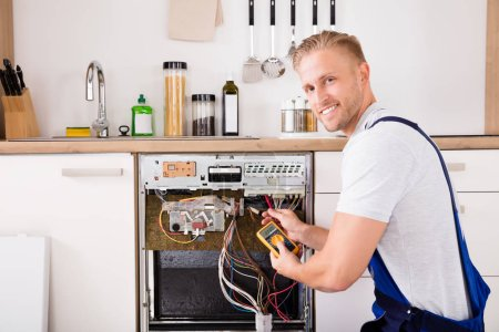 Photo for Young Male Technician Checking Dishwasher With Digital Multimeter In Kitchen - Royalty Free Image