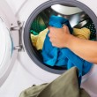 Closeup Of Woman Hand Loading Dirty Clothes In Was...
