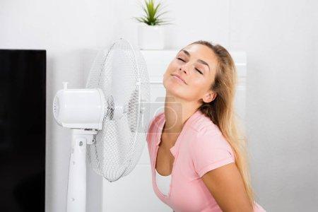 Foto de Joven sonriente mujer sentada en sofá delante de ventilador durante tiempo caliente en casa - Imagen libre de derechos