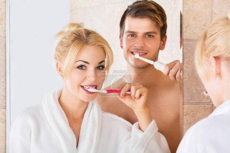 Photo pour Jeune couple souriant regardant miroir brossant dents ensemble dans la salle de bain à la maison - image libre de droit