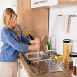 Young Woman Using Plunger In Blocked Kitchen Sink ...
