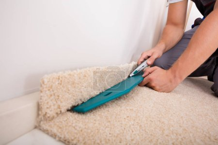 Photo for Closeup Of Craftsman Fitting Carpet On Floor With Cutter - Royalty Free Image