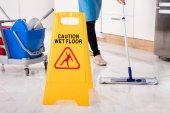 Yellow Wet Caution Sign On Wet Floor In Kitchen