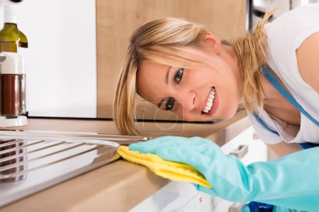 Woman Cleaning Kitchen Worktop