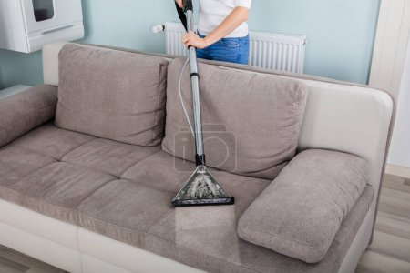 Woman Cleaning Sofa With Vacuum Cleaner At Home...