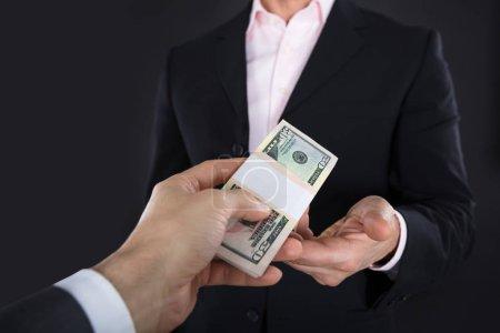 Photo pour Gros plan d'homme d'affaires recevant des billets sur fond noir - image libre de droit