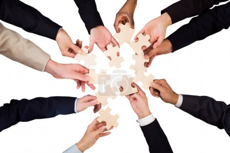 Photo for High Angle View Of Businesspeople Hands Holding Puzzles On White Background - Royalty Free Image