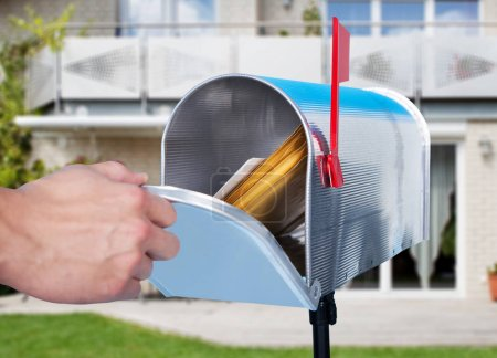Photo for Close-up Of Human Hand Checking Mailbox Outside House - Royalty Free Image