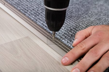 Photo for Human Hand Installing Carpet On Floor Using Wireless Screwdriver - Royalty Free Image