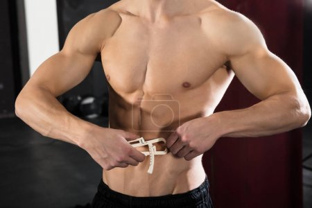 Man Measuring Body Fat With Caliper
