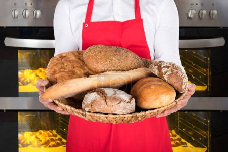 Photo for Man Holding Plate With Breads And Buns In Front Of Oven - Royalty Free Image