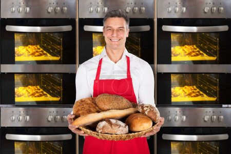 Photo for Smiling Baker Holding A Wicker Basket With Bread In Front Of Oven - Royalty Free Image