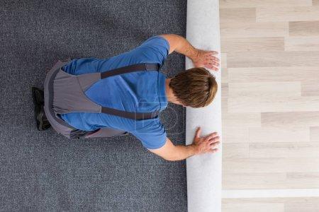 Male Worker Rolling Carpet