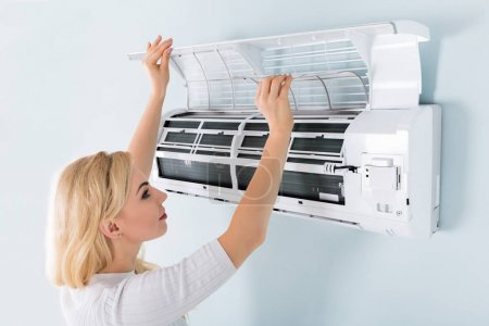 Woman Cleaning Air Conditioning System