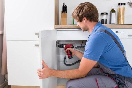Male Handyman Fixing Cabinet