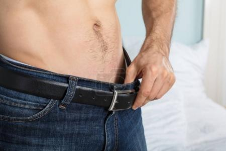 Photo for Closeup Of Person Looking Inside His Jeans At Home - Royalty Free Image