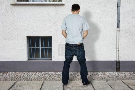 Homme pipi sur le mur du bâtiment