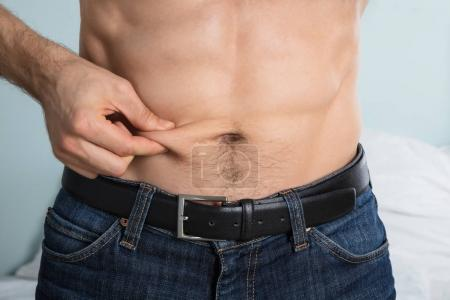 Person Measuring Fat On Belly
