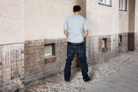 Homme pipi sur le mur