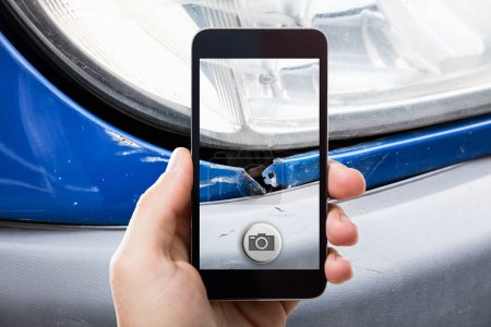 Photo for Closeup Of Person Taking Picture Of Damaged Car On Mobile Phone - Royalty Free Image