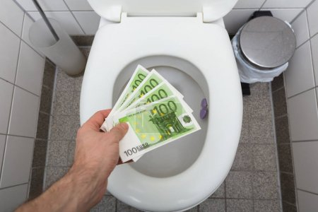 Photo for Elevated View Of A Man Throwing Hundred Euro Notes In Toilet - Royalty Free Image