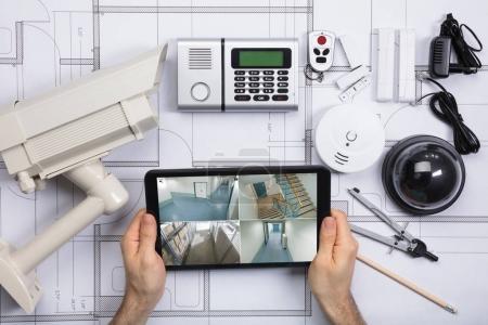 Photo pour Gros plan de personne regardant avec sur tablette numérique avec des équipements de sécurité sur le plan d'action - image libre de droit