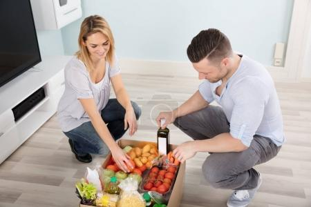 Couple Looking At Groceries