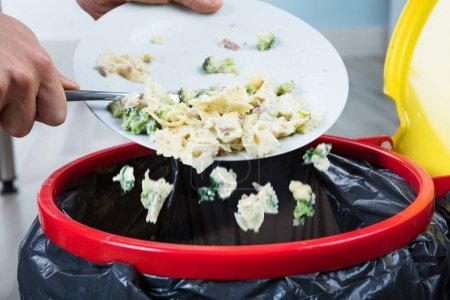 Person Throwing Pasta In Trash Bin
