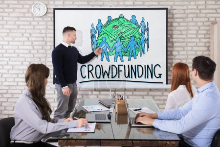 Businessman Showing Crowd Funding Concept On Whiteboard To His Colleague In Office
