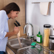 Young Woman Using Plunger In Blocked Kitchen Sink...