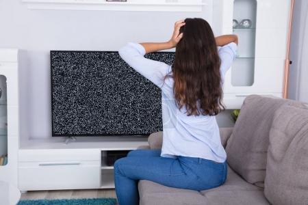 Photo pour Vue arrière de la femme sur le canapé frustré avec Glitch écran du téléviseur à la maison - image libre de droit