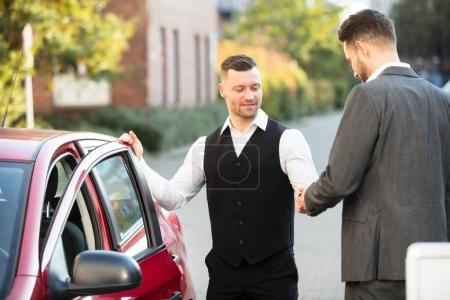 Valet And Businessperson Near Car
