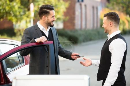 Businessman Giving Key To Valet