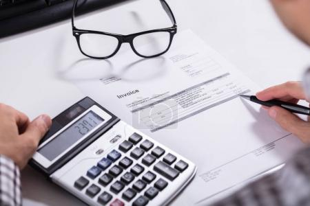 Close-up Of Businessman's Hands Calculating Invoice Using Calculator With Eyeglasses On Desk