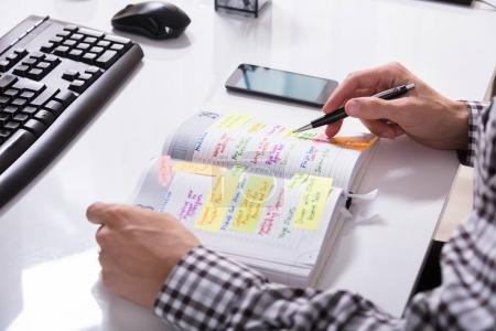 Close-up Of A Businessperson With Mobile Phone Writing Schedule In Diary On Desk