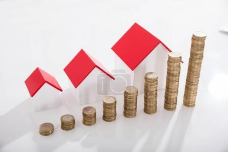 Elevated View Of House Models And Stack Of Coins On White Desk