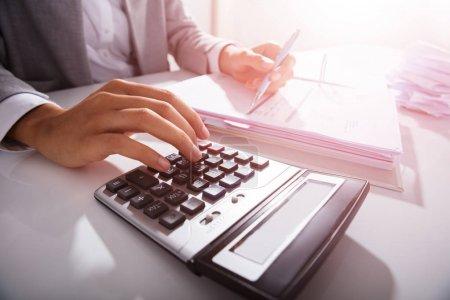 Photo pour Gros plan de l'homme d'affaires Calcul des factures avec calculatrice dans le bureau - image libre de droit